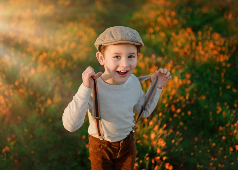 Newsies Hat wearing toddler boy playing with his suspenders in a California Poppy Field