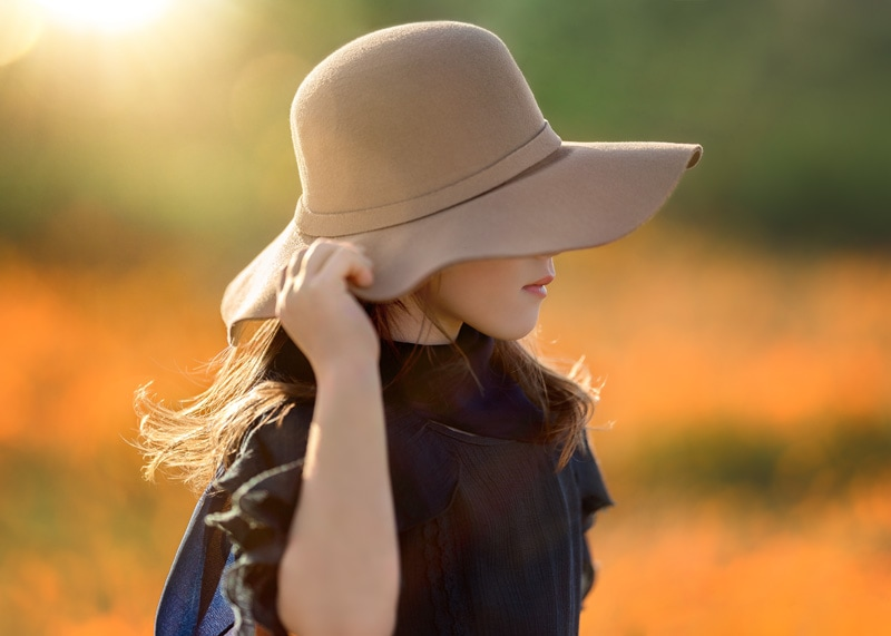 Candid Profile of Young Girl with Audrey Hepburn Floppy Hat surrounded by California Poppies
