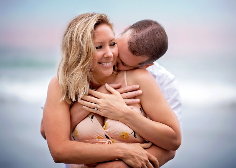 Couples Photography, Man giving woman a kiss on her neck from behind, and woman peering over to her side smiling at the beach portrait