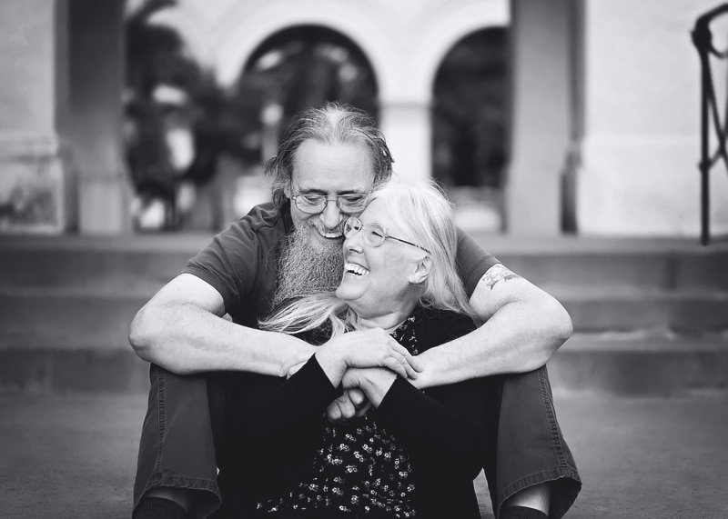 Couples Photography, Grandparents sitting on steps embracing each other in a laugh in a black and white portrait
