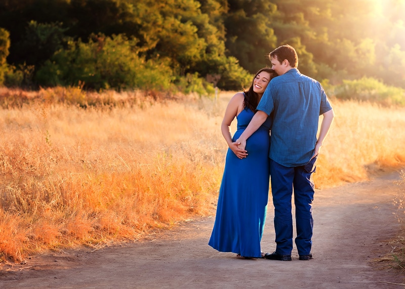 Maternity photography, couple standing together on dirt road