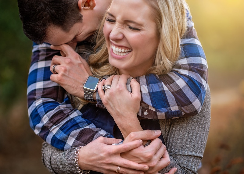 Couples Photography, Couple embracing each other in a candid image of them both hysterically laughing with eyes closed