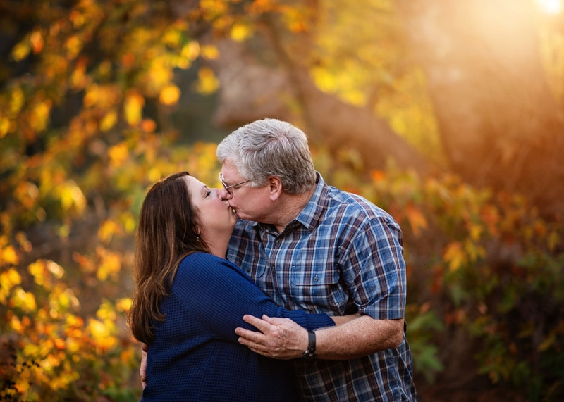Couples Photography, Grandparents embracing each other and kissing in the fall golden sunset portrait