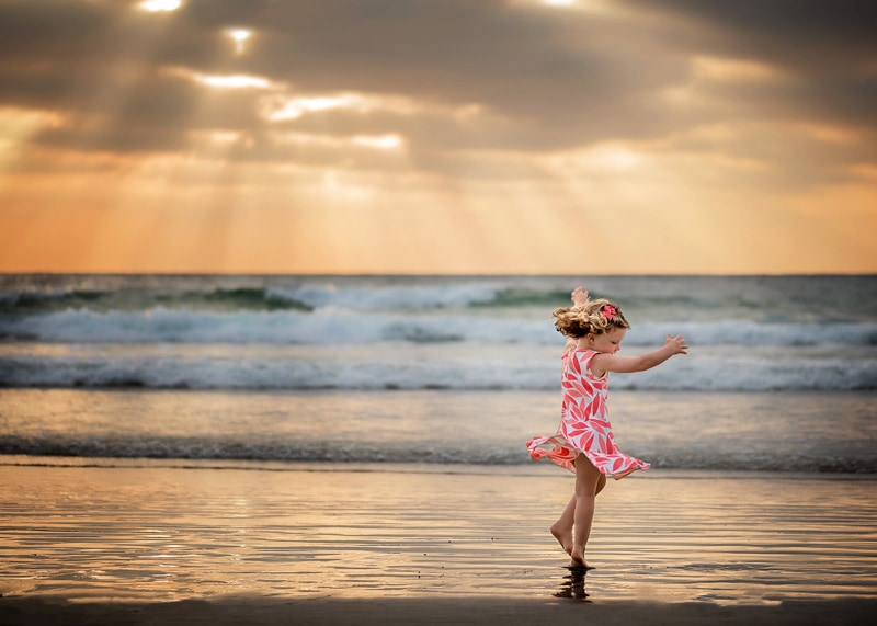 Child Photography, Toddler girl dancing in the sunset light at the beach portrait