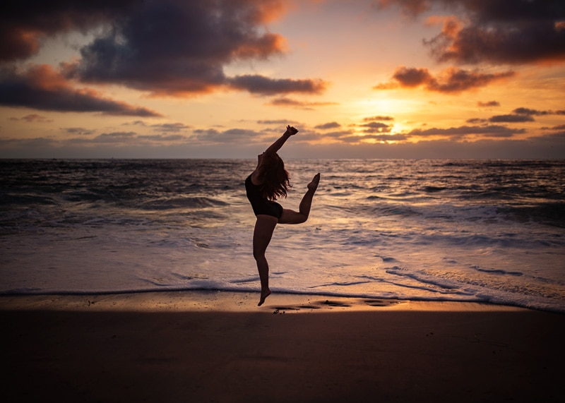 Senior Photography, Senior girl caught in a silhouette dancing in the golden purple sunset at the beach portrait