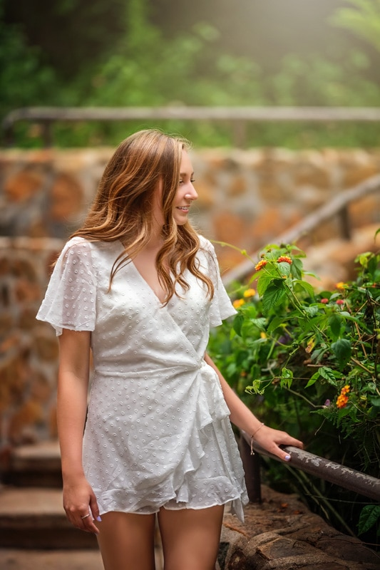 Beautiful Senior girl in white romper walking down a flight of stairs surrounded by greenery in San Diego