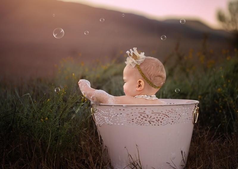 Child Photography, Baby girl celebrating her one year birthday by taking a bubble bath in a field with a princess crown portrait