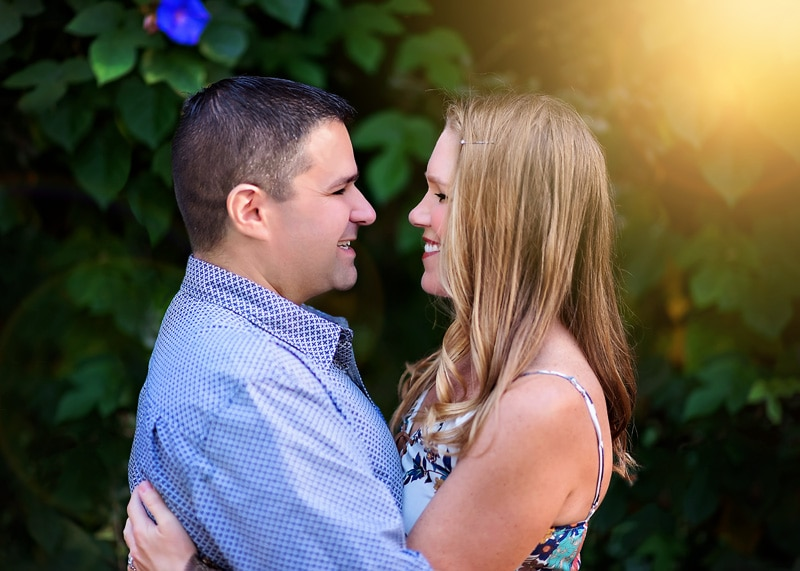 Couples Photography, Couple embracing each other looking directly at each other with a beautiful morning glory filled wall behind them portrait