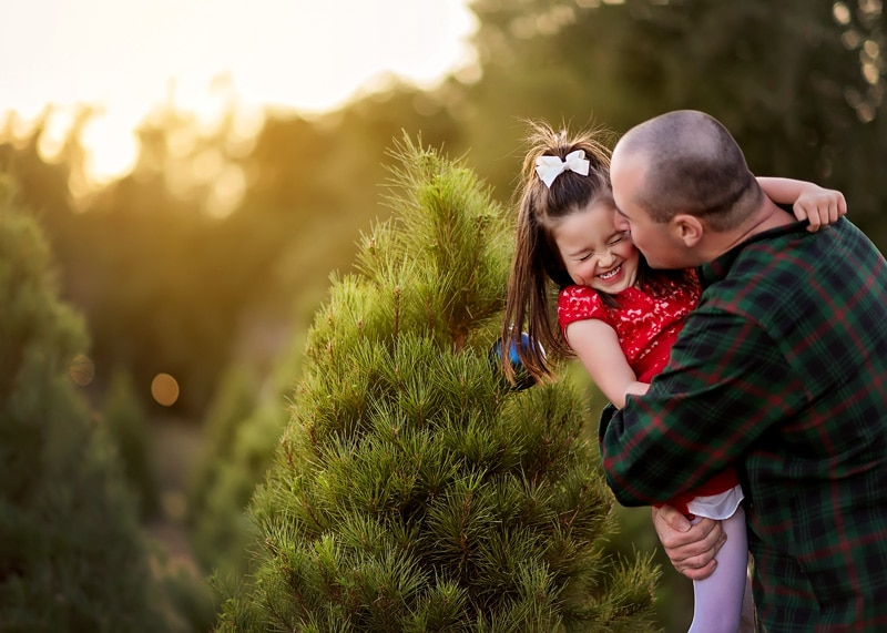 Family Photography, father giving daughter a kiss at christmas tree farm