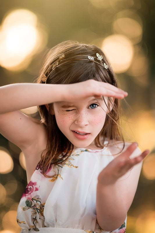 Little Girl in White Floral Chiffon Dress squinting at the camera with beautiful golden bokeh in background in San Diego