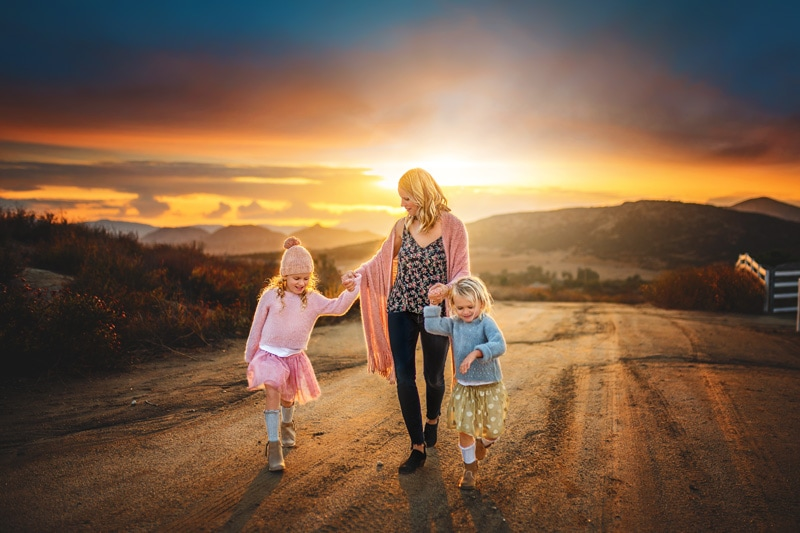 A beautiful moment between a mother and her two daughters candidly walking as the sun sets behind them on a rustic ranch in Temecula California