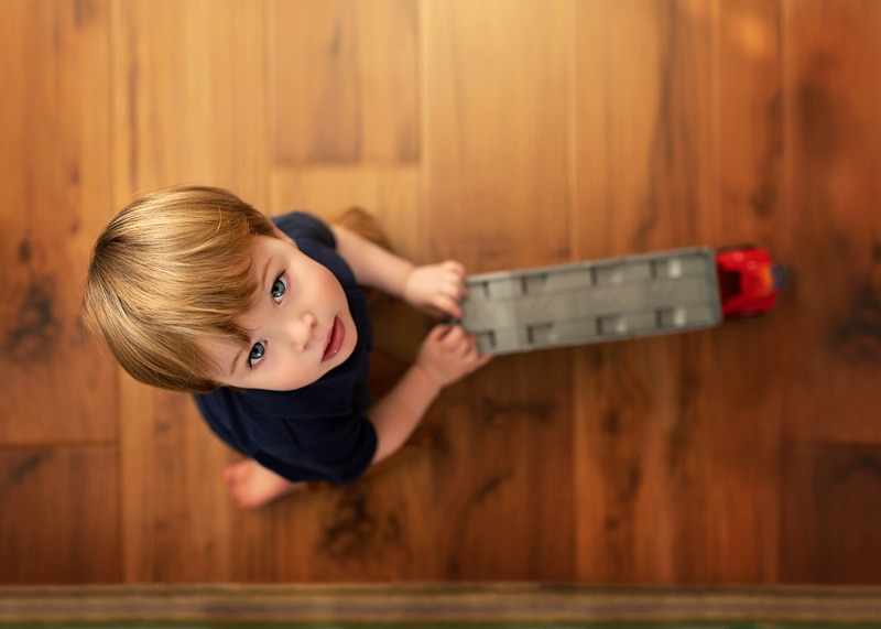 Lifestyle Photography, looking down at little boy playing with truck
