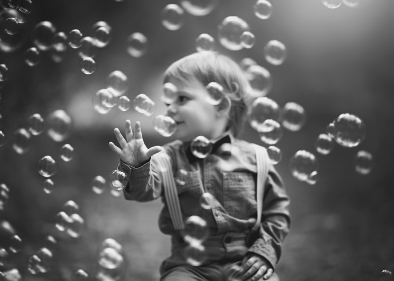 Child Photography, Toddler boy catching and popping bubbles in a unique black and white matte film portrait