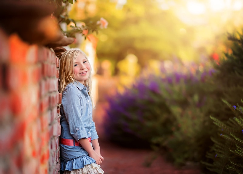 Child Photography, Elementary aged girl standing against a brick wall peering over at the camera with beautiful purple and green foliage in the background