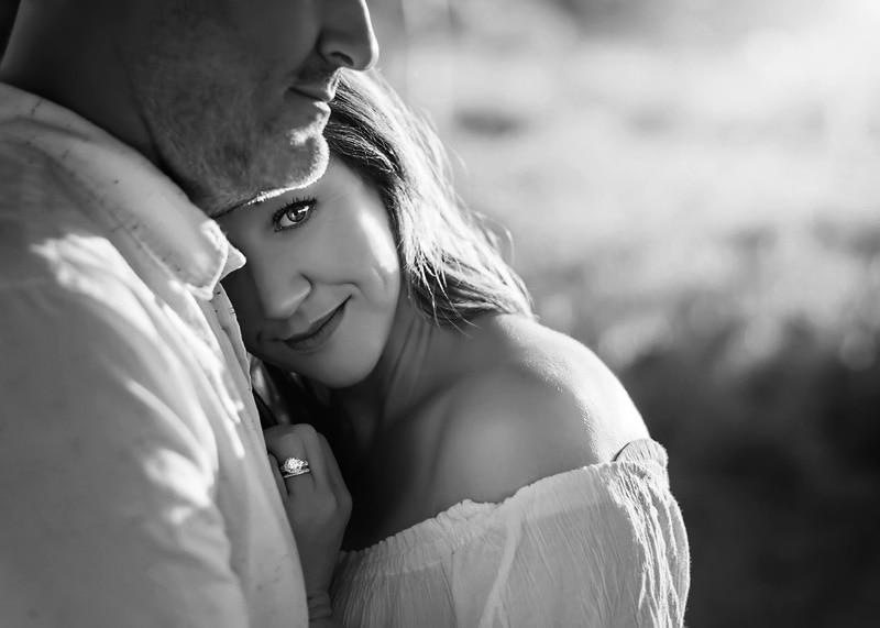 Couples Photography, Black and white portrait of woman leaning up against husband with her looking directly at camera portrait