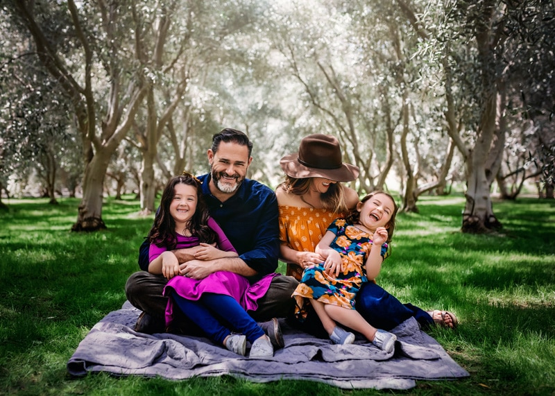 Happy family giggling on the grass surrounded by olive trees