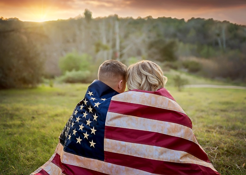 Couples Photography, Backshot of couple embracing each other being wrapped in a tea-dyed american flag at sunset portrait