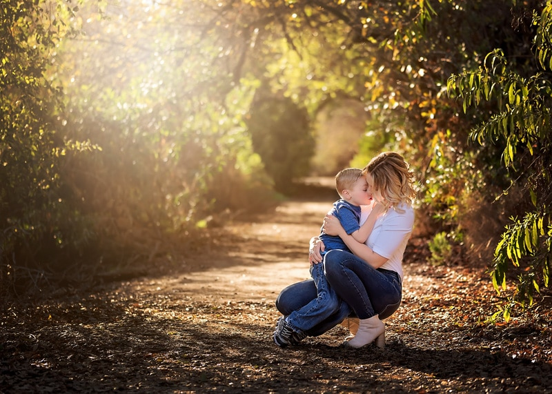 Family Photography, mother kneeling down to kiss little boy