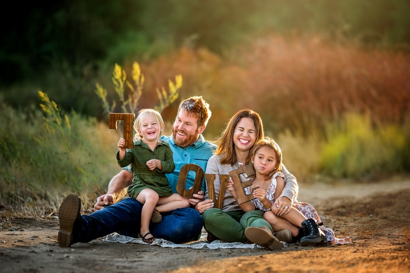 A family of four having fun during a session and giggling as they watch the sunset in a Temecula rustic location