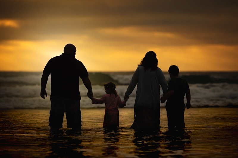 A golden silhouette sunset of a family of four in the water at a San Diego beach