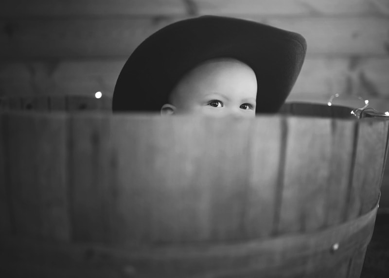 Child Photography, Baby boy dressed as a cowboy playing hide and go seek in a barn barrel in a black and white portrait