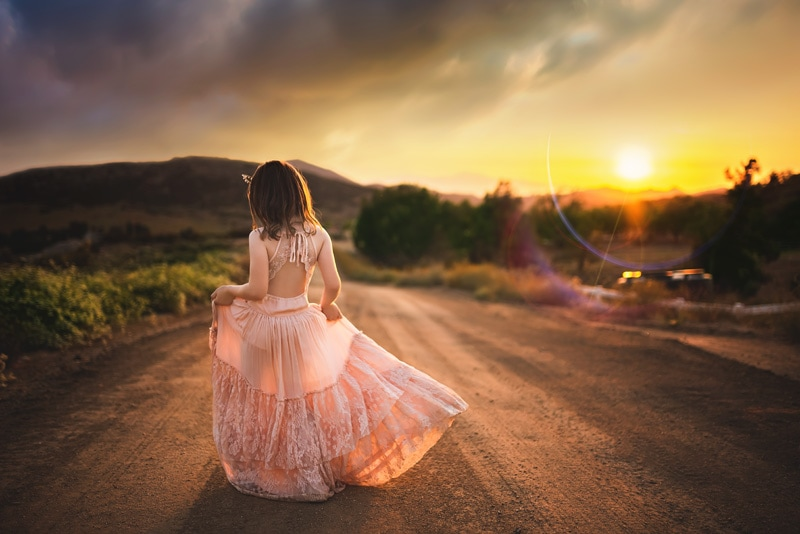 Little girl in pink lace maxi dress walking down a dirt rustic road during sunset hours in Temecula