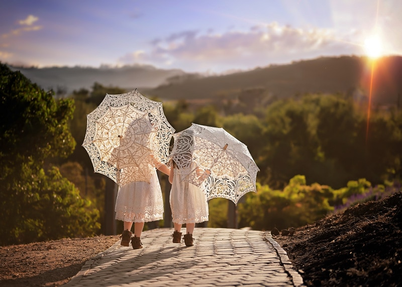 Child Photography, Toddler girls walking along a brick path carrying parasols with beautiful mountains ahead of them portrait