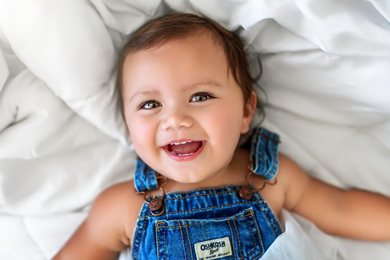 Beautiful one year old little girl laying on her parents white bed looking up at the camera in San Diego