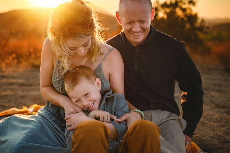 Giggles galore for this family of three watching the golden sunset on a Temecula rustic Ranch