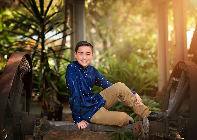 Child Photography, Teenage boy sitting atop of a wooden wheel axel at a botanical garden smiling at the camera portrait