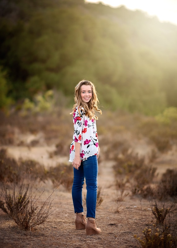 Child Photography, Teenage girl walking along in a nature preserve and caught turning around to peer at the camera portrait