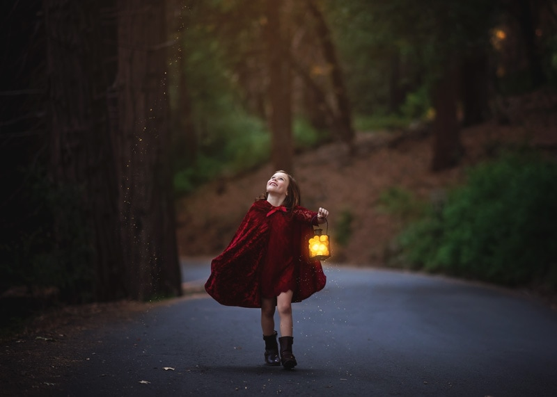 Child Photography, Toddler girl smiling while wearing a red riding hood costume holding a lit lantern in the dark forest portrait