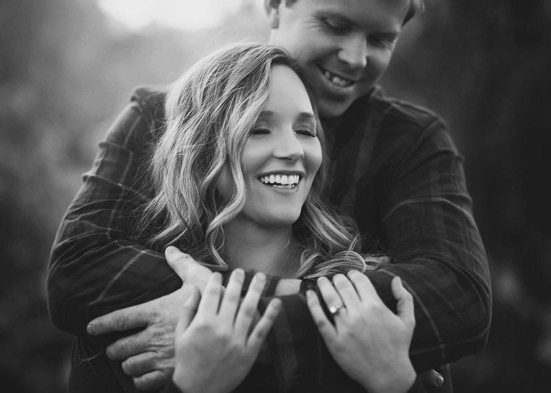 Couples Photography, Man embracing woman in a hug from behind while she giggles with her eyes closed in black and white portrait
