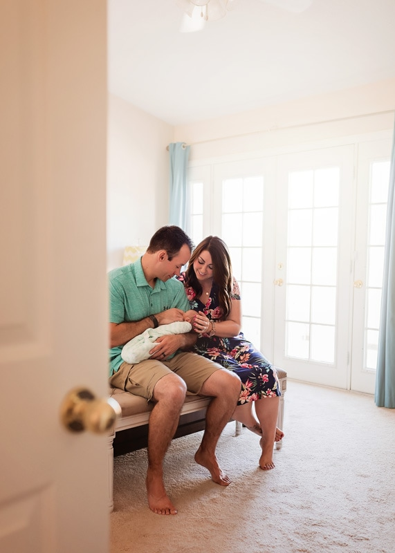 Lifestyle Photography, looking at a couple with their new baby through doorway