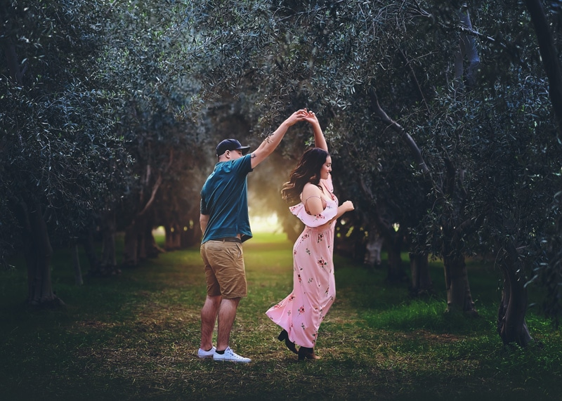 Couples Photography, Couple surrounded in olive trees backlit by the sun while twirling and dancing in the light portrait