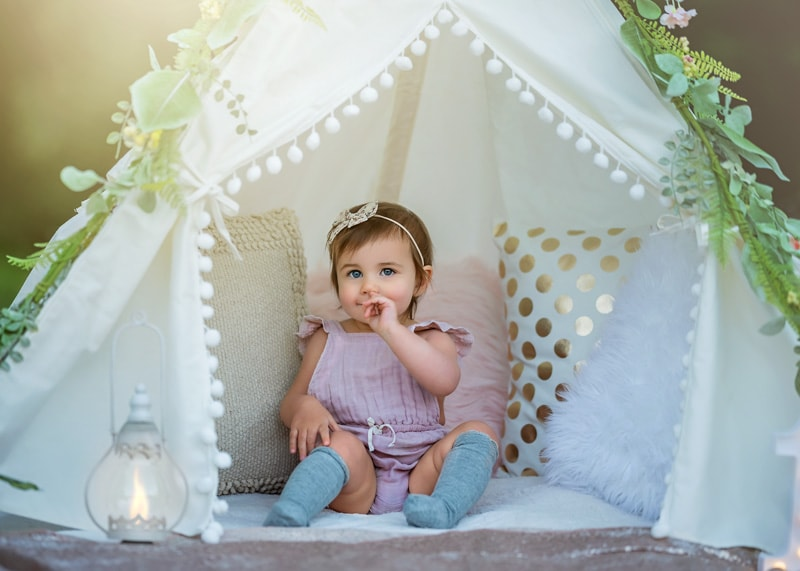 Child Photography, Toddler girl dressed in shabby chic attire in white tent filled with pillows playing coy portrait