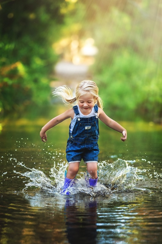 Toddler Girl in pigtails and Osh Kosh Overalls splashing with purple rain boots in a creek In San Diego