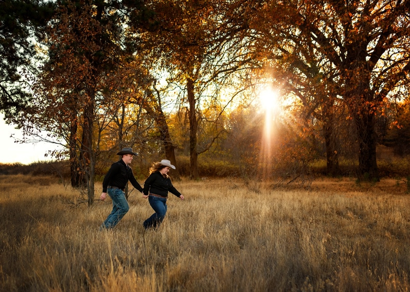 Couples Photography, Couple running through the fields at sunset dressed in their best cowboy outfits laughing portrait