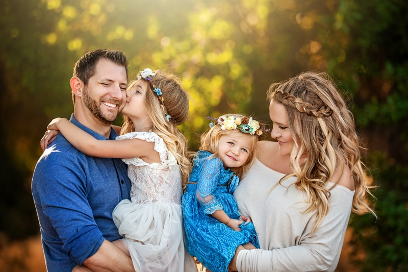 A beautiful family with daughters giving kisses to their parents in a rustic Temecula setting