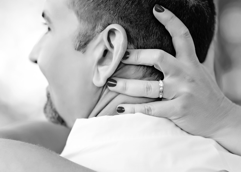 Couples Photography, Detailed shot of engagement diamond ring on a woman's hand while embracing the man in a hug black and white portrait
