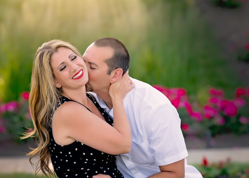 Couples Photography, Engaged couple laughing and enjoying a moment while man kisses woman on the neck with fuchsia colored flowers in the background portrait