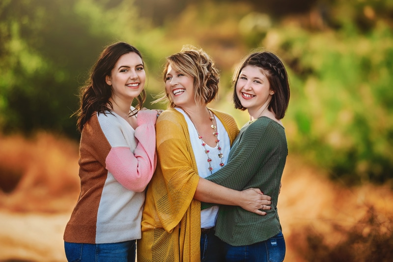 Beautiful mother and daughters laughingly looking at each other in a Temecula ranch rustic setting
