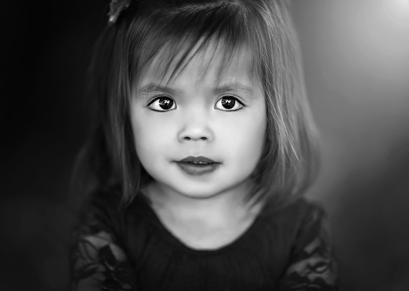 Child Photography, Toddler girl posed in front of a camera looking to the lens in a black and white portrait