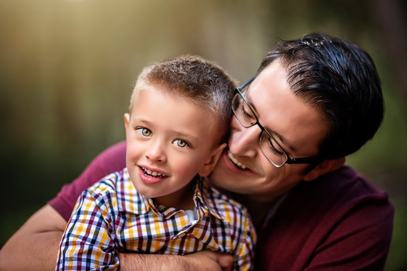 Family Photography, little boy in plaid in daddy's lap