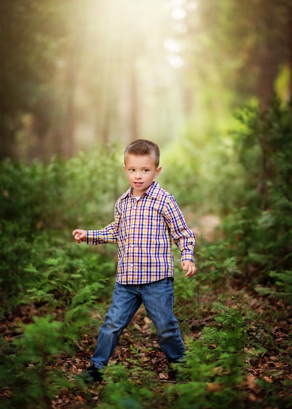 Child Photography, Toddler boy walking along the sunlit deep green forest portrait