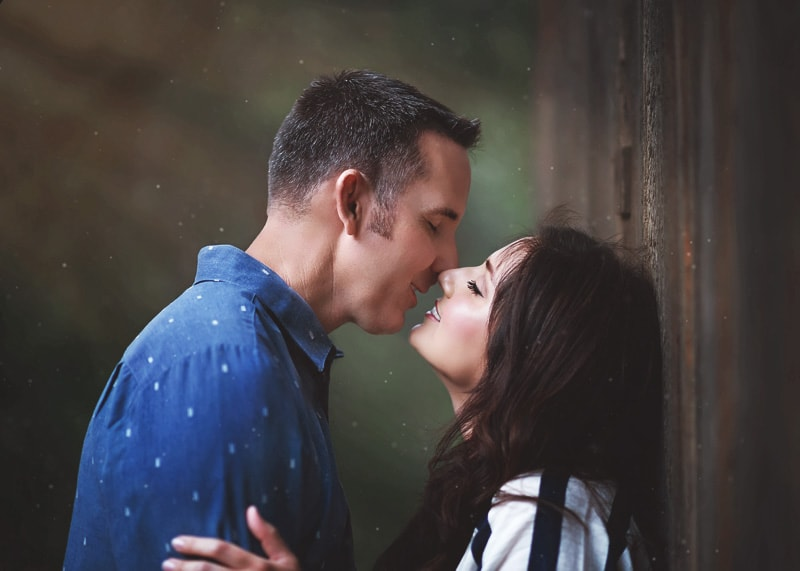 Couples Photography, Couple enjoying the closeness of each other about to kiss against an old dark brown barn portrait