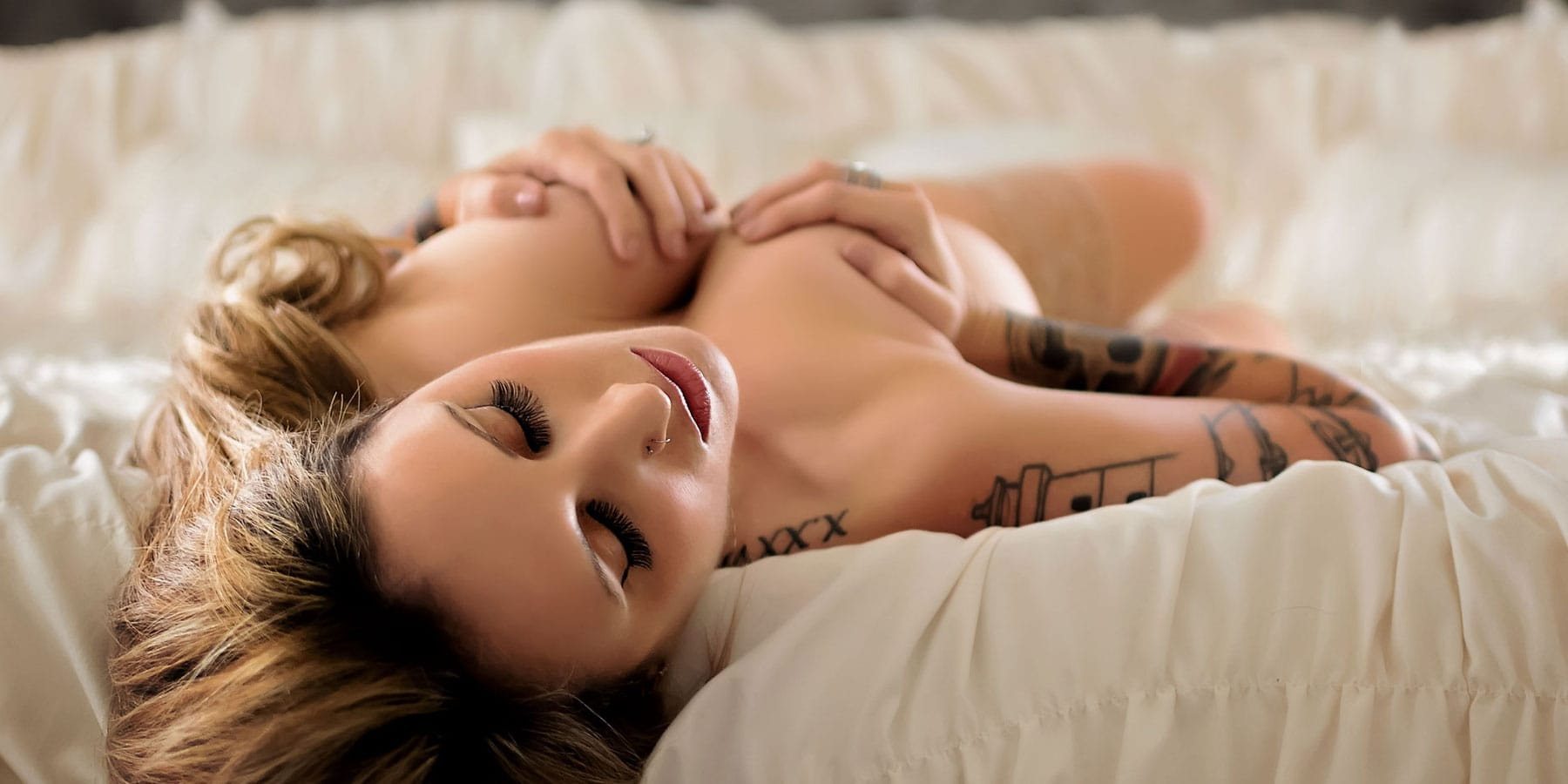 Boudoir Photography, tattooed woman laying on her back in bed